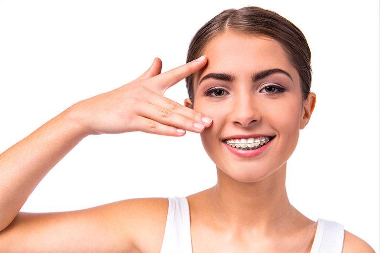 Clinica luz dental. Chica con ortodoncia tras someterse a implantes dentales
